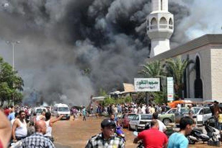 Asap hitam mengepul di dekat sebuah masjid di kota Tripoli, Lebanon setelah sebuah bom mobil meledak usai ibadah shalat Jumat (23/8/2013), menewaskan sedikitnya 27 orang.