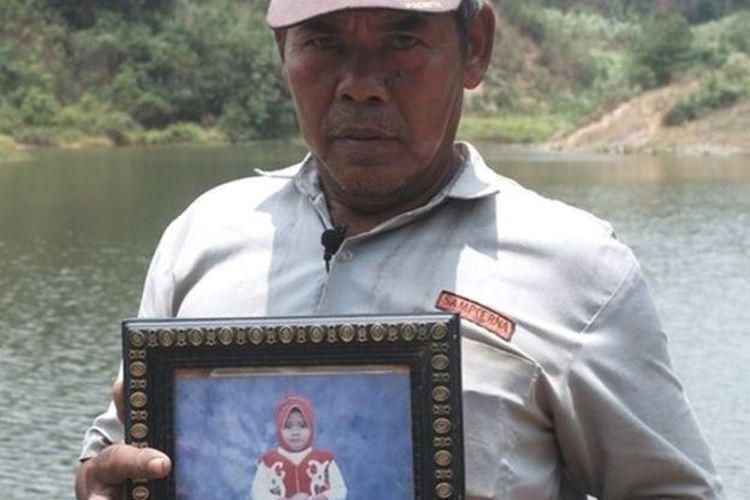Kardi memegang potret cucunya yang tewas tenggelam di lubang tambang. Kalau mata dibutakan, saya sudah balas dendam, ujarnya.