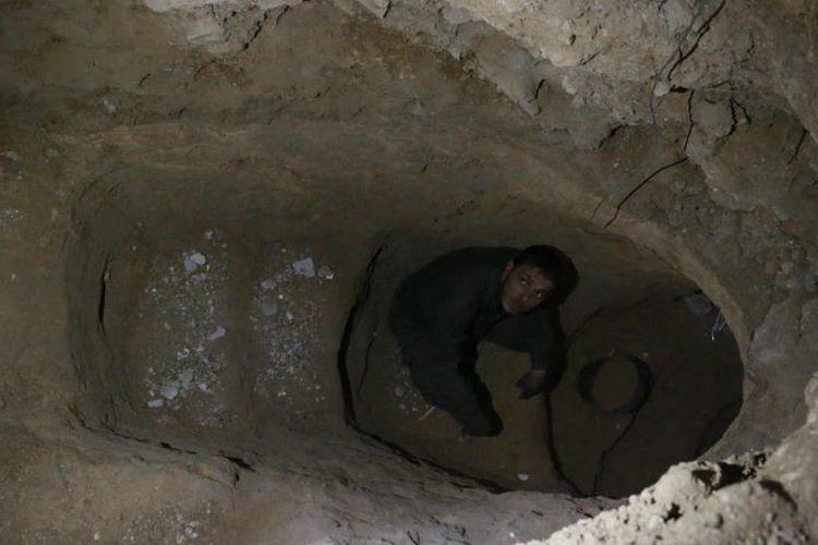 Salah seorang warga beristirahat di sela pekerjaan membuat lubang perlindungan.