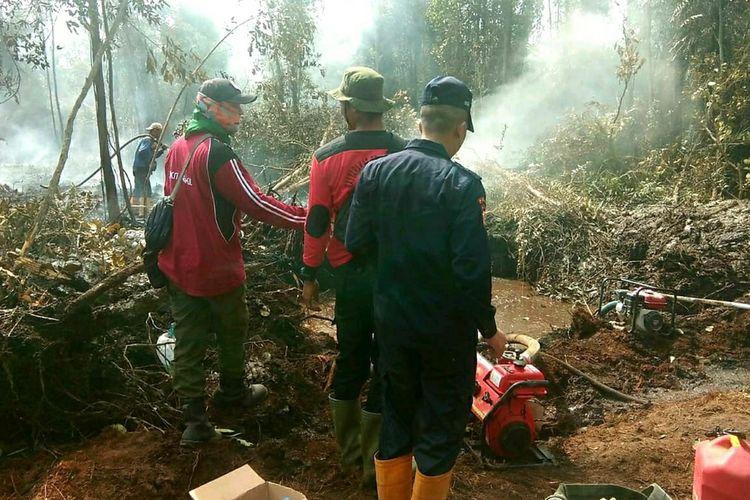 Petugas gabungan berupaya memadamkan api karhutla di kawasan hutan konservasi cagar biosfer Giam Siak Kecil di Desa Bukit Kerikil, Kecamatan Bukit Batu, Kabupaten Bengkalis, Riau, Kamis (16/1/2020).