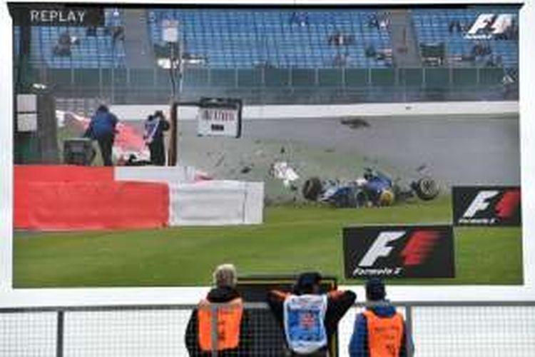 Petugas lintasan melihat layar besar yang memperlihatkan kecelakaan pebalap Sauber asal Swedia, Marcus Ericsson, pada sesi latihan ketiga GP Inggris di Sirkuit Silverstone, Sabtu (9/7/2016).