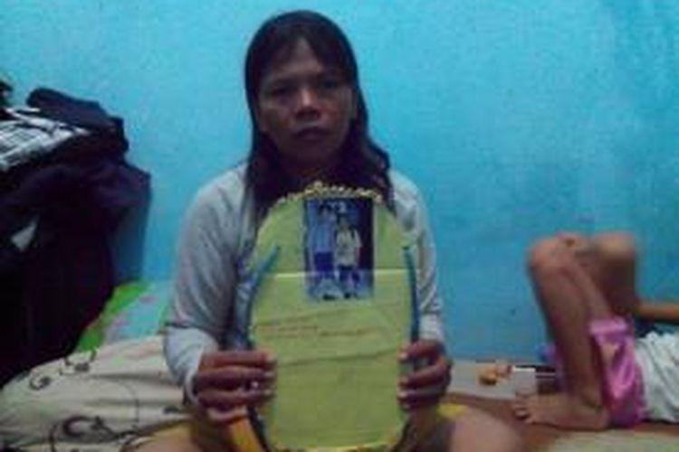 Ibu Evan Christoper, Ratna Dumiarti, memegang papan nama yang dibawa anaknya saat MOS di SMP Flora, Bekasi Utara.