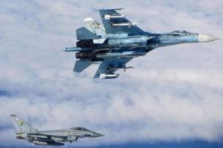Sebuah pesawat tempur Sukhoi Su-27 (atas) milik Rusia diawasi sebuah pesawat tempur Royal Air Force (RAF) Typhoon Inggris (bawah) saat sejumlah pesawat militer Rusia terbang di wilayah udara internasional dekat negara-negara Baltik, Senin (16/6/2014)