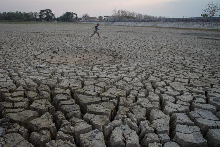 Warga melintas di waduk yang kering Desa Simo, Kradenan, Grobogan, Jawa Tengah, Rabu (25/9/2019). Badan Meteorologi, Klimatologi, dan Geofisika (BMKG) memprediksi musim kemarau panjang dengan kekeringan ekstrem masih akan terjadi di sejumlah wilayah di Indonesia hingga bulan November 2019. ANTARA FOTO/Mohammad Ayudha/nz.
