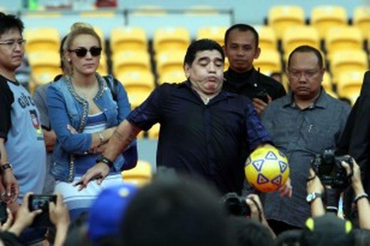 Pesepak bola legendaris asal Argentina, Diego Maradona di Stadion Utama Gelora Bung Karno (SUGBK), Jakarta Pusat, Sabtu (29/6/2013). Maradona akhirnya menyapa para penggemarnya di Indonesia dengan membagi-bagikan bola yang telah ditandatanganinya.