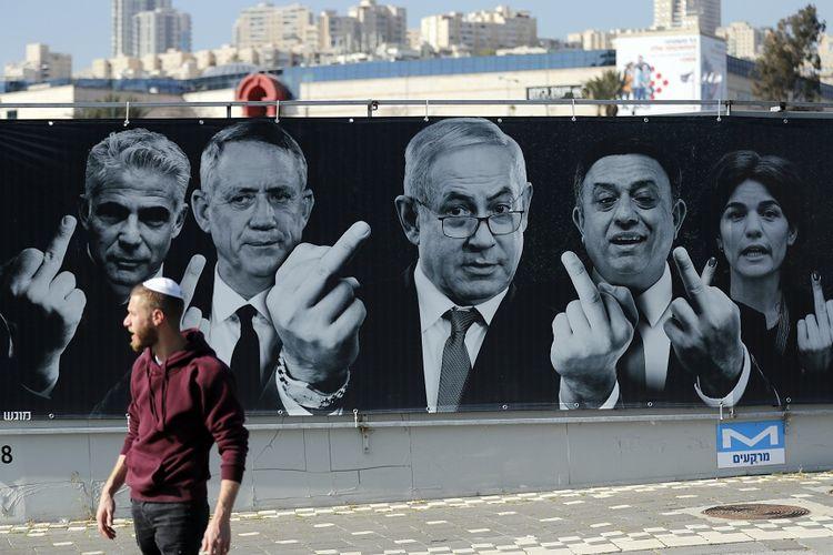 Seorang warga Israel berjalan melewati sebuah poster kampanye pemilu yang menampilkan para politisi mengacungkan jari tengah, yang terpasang di Yerusalem.