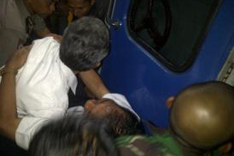 Seorang korban kecelakaan KA Malabar diangkat oleh petugas yang dibantu warga di Stasiun Cirahayu, Kecamatan Ciawi, Kabupaten Tasikmalaya, Sabtu (5/4/2014) dini hari. Kecelakaan anjlok di kawasan ini, Jumat (4/4/2014) malam.