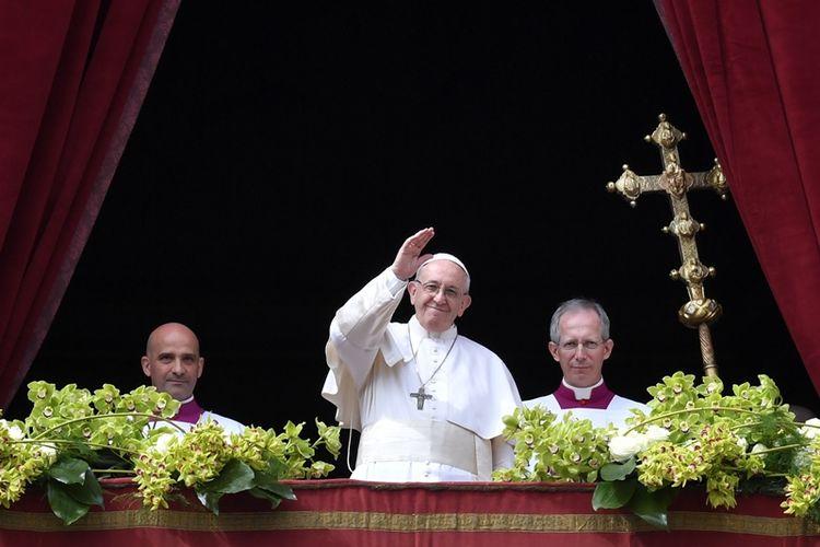 Paus Fransiskus menyampaikan berkat Urbi et Orbi kepada kota dan dunia dari balkon basilika Santo Petrus, setelah Misa Paskah Paskah, Minggu (1/4/2018) di Vatikan. (AFP/Andreas Splaro)]