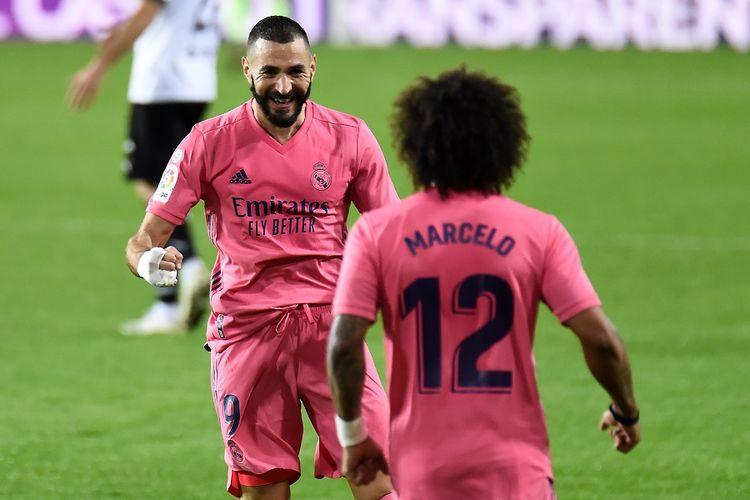 Penyerang Real Madrid Karim Benzema merayakan gol bersama bek Real Madrid Marcelo (kanan) setelah mencetak gol dalam pertandingan Liga Spanyol antara Valencia vs Real Madrid di Stadion Mestalla di Valencia pada 8 November 2020.