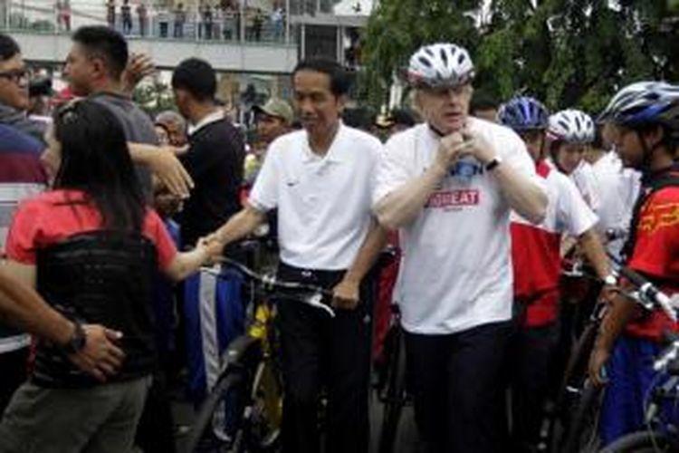 Presiden Joko Widodo bersama Wali Kota London Boris Johnson bersiap bersepeda saat car free day, di kawasan Bundaran Hotel Indonesia, Jakarta, Minggu (30/11/2014). Pada acara ini Jokowi juga menyaksikan penyerahan sepeda secara simbolik dari Pemerintah Kota London kepada Pemerintah Provinsi DKI Jakarta.