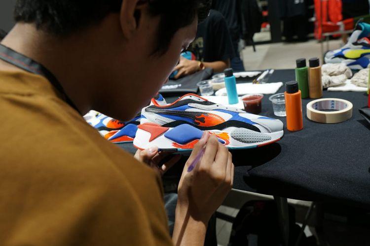 Salah satu peserta workshop customize sneaker Puma RS-X3 di Gerai Puma, Senayan City, sedang berkreasi dengan cat akrilik dan kuas.