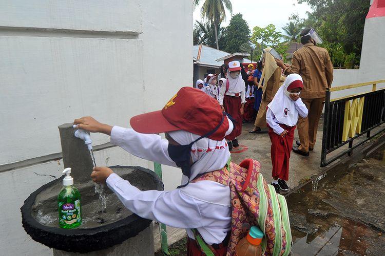 Sejumlah murid mencuci tangan sebelum masuk hari pertama sekolah di SDN 11 Marunggi Pariaman, Sumatera Barat, Senin (13/7/2020). Kota Pariaman bersama Kabupaten Pesisir Selatan, Kota Sawahlunto dan Kabupaten Pasaman Barat merupakan empat daerah di zona hijau di Sumatera Barat yang sudah memulai aktivitas belajar-mengajar di sekolah dengan pola tatap muka langsung dan menerapkan protokol kesehatan COVID-19.