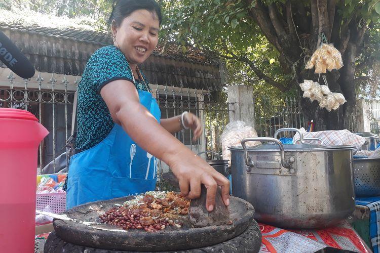 Ibu Mella, penjual rujak cingur seharga Rp 60.000 di Wiguna Timur, Kelurahan Gunung Anyar, Kecamatan Rungkut, Surabaya, melayani pembeli, Rabu (12/6/2019).