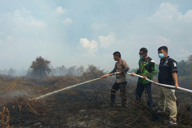 Petugas kepolisian dari Polresta Pontianak saat memadamkan kebakaran lahan yang terjadi di Sekunder C, Kecamatan Rasau Jaya, Kabupaten Kubu Raya  (24/7/2018).