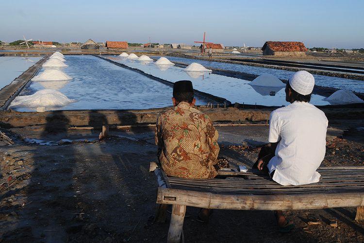 Foto dirilis Senin (2/11/2020), memperlihatkan petani berbincang sambil memandangi tumpukan garam yang baru dipanen di Desa Bunder, Pamekasan, Jawa Timur.