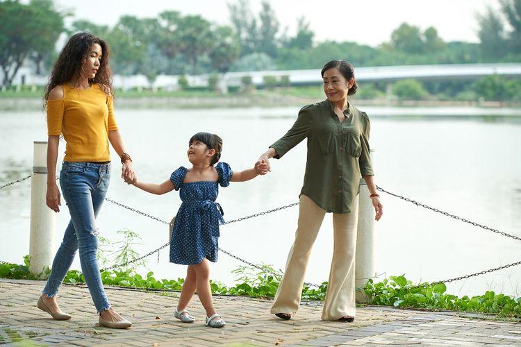 Ilustrasi ibu, anak, dan cucu sedang berjalan-jalan di taman.