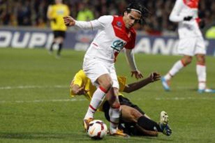 Striker AS Monaco, Radamel Falcao (kiri), ditekel oleh bek Chasselay, Soner Ertek (kuning), pada laga Coupe de France di Stade de Gerland, Lyon, Rabu (22/1/2014). Tekel tersebut membuat Falcao mengalami cedera lutut.