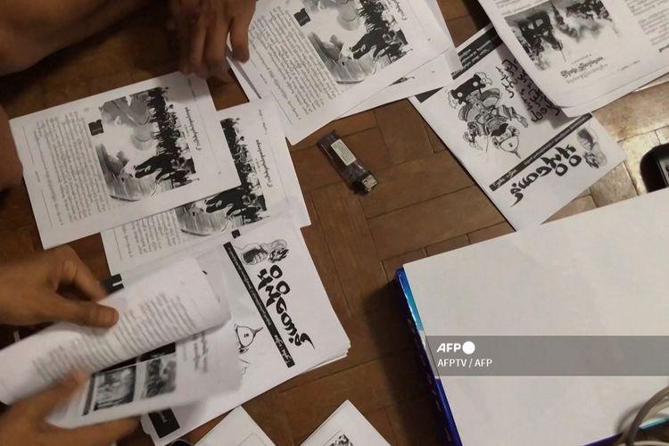 Tangkap layar video AFPTV yang diambil pada 10 April 2021 menunjukkan buletin ilegal yang diproduksi untuk menyebarkan informasi di Yangon.
