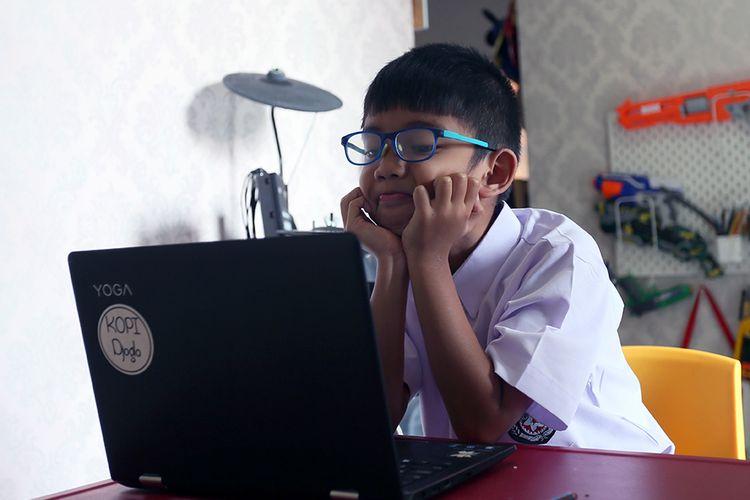Seorang murid baru tingkat Sekolah Dasar (SD) mengikuti Masa Pengenalan Lingkungan Sekolah (MPLS) secara daring dari rumahnya di Blitar, Jawa Timur, Senin (13/7/2020). Memasuki masa hari pertama masuk sekolah tahun ajaran baru 2020 ini, Kemendikbud hanya memberikan ijin pemberlakuan masuk sekolah secara tatap muka terhadap 104 kabupaten/kota di seluruh indonesia yang termasuk zona hijau dalam peta penyebaran COVID-19, sedangkan bagi kabupaten/kota lainnya yang masih termasuk dalam zona kuning dan merah, masih harus memberlakukan pembelajaran melalui sistem daring dari rumah.