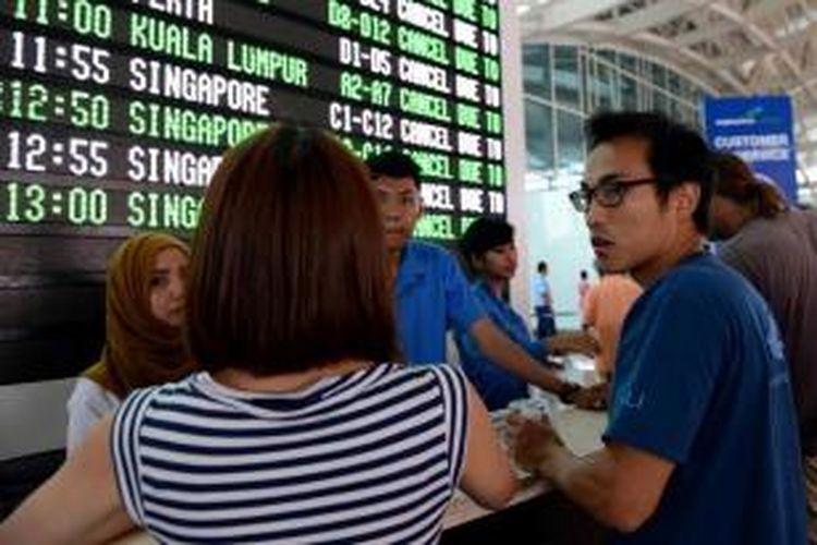 Penumpang menunggu informasi mengenai penerbangan yang ditunda dan dibatalkan di area keberangkatan Bandara Internasional Ngurah Rai, Denpasar, 4 November 2015. Penutupan bandara diperpanjang aktivitas Gunung Barujari yang meningkat. Debu vulkaniknya yang menuju Bali dinilai membahayakan penerbangan.