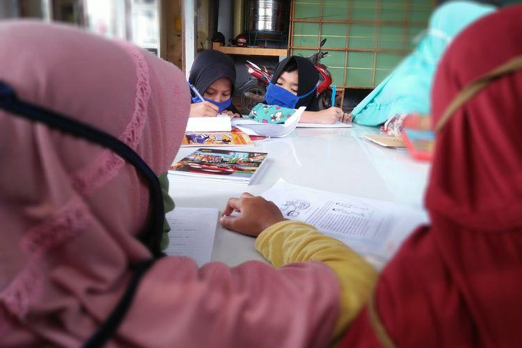Dua anak asuh PA Pelita Harapan Bangsa sedang menyalin dan mengerjakan tugas dalam pembelajaran daring, Rabu (14/10/2020) pagi. Sebanyak 24 siswi di panti asuhan itu terpaksa bergantian menggunakan ponsel untuk belajar daring.