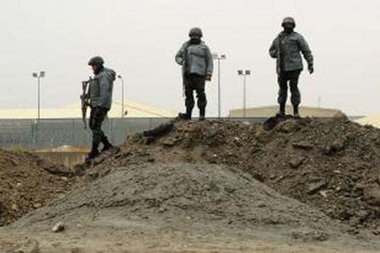 Polisi Afganistan berjaga-jaga di sekitar lokasi serangan bom mobil bunuh diri terhadap konvoi militer NATO yang akan memasuki bandara internasional Kabul, Rabu (11/12/2013).