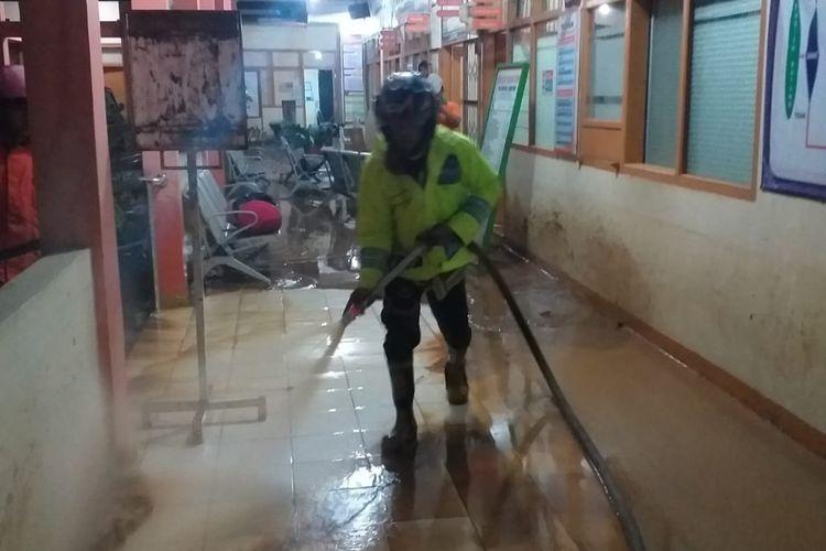 Petugas Rescue Damkar Agam membersihkan ruangan Puskesmas yang dihantam banjir bandang, Jumat (20/12/2019)