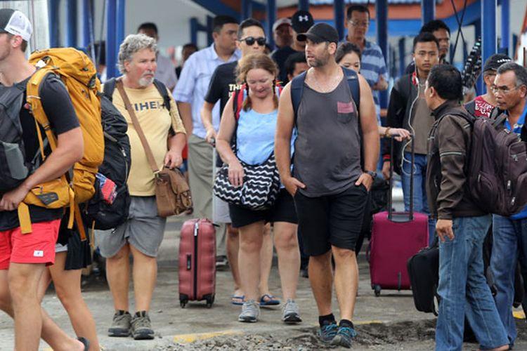 Wisatawan asing dari Bali turun dari kapal di Pelabuhan Ketapang, Banyuwangi, Jawa Timur, Rabu (29/11/2017). Meletusnya Gunung Agung di Bali berdampak pada jumlah wisatawan dari Bali menuju Jawa melalui pelabuhan Ketapang meningkat 113 persen dari biasanya 1.112 penumpang, dan data PT ASDP Ketapang, peningkatan terbesar terjadi pada angkutan bus dan travel mencapai 807 persen atau 417 armada.