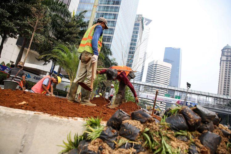 Pekerja menyelesaikan revitalisasi trotoar dan taman di kawasan jalan Sudirman, Jakarta Pusat, Kamis (19/7/2018). Penataan trotoar dan taman ditargetkan selesai pada akhir bulan Juli sebelum pelaksanaan Asian Games 2018.