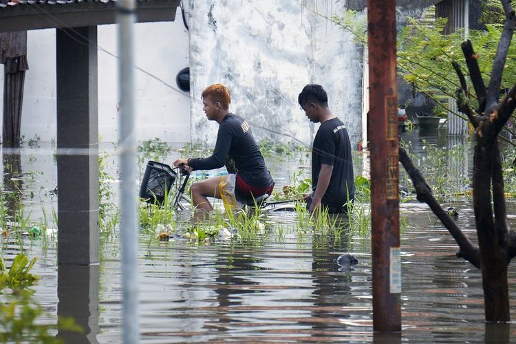 Warga melewati jalan desa yang terendam banjir di Tirto, Pekalongan, Jawa Tengah, Senin (24/2/2020). Berdasarkan data Badan Penanggulangan Bencana Daerah (BPBD) Kota Pekalongan, sebanyak sekitar 80 persen wilayah Kota Pekalongan terdampak banjir akibat hujan sejak Minggu (23/2) sore dengan ketinggian air rata-rata mencapai 30-100 cm. ANTARA FOTO/Harviyan Perdana Putra/aww.