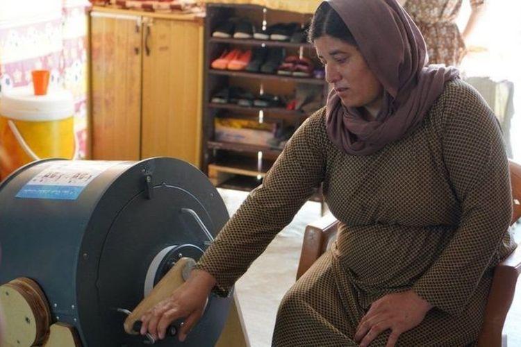 Seorang perempuan mengoperasikan Divya, mesin cuci tanpa listrik yang diputar dengan tangan.