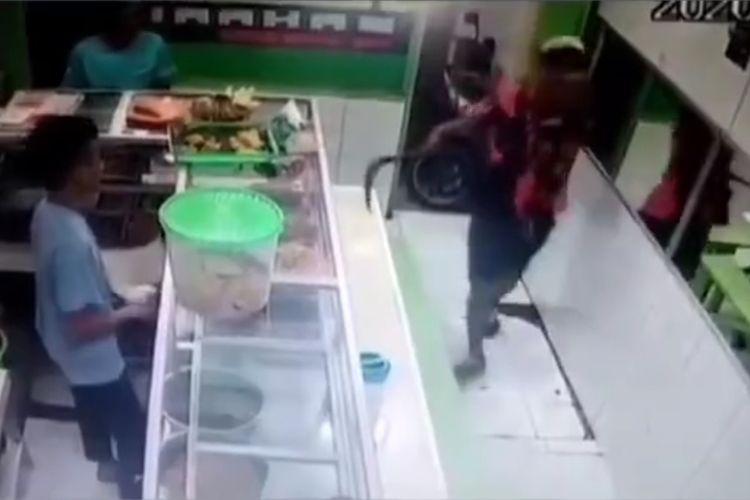 Tangkapan layar akun instagram @infojktku atas aksi seorang pria yang mengacungkan celurit di sebuah warung makan di Kembangan