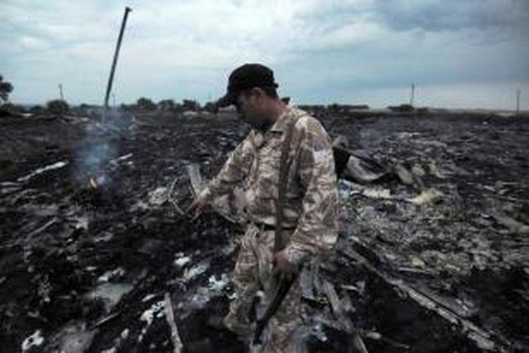 Seorang pria mengenakan seragam militer berada di dekat puing pesawat Malaysia Airlines yang membawa 295 orang penumpang dari Amsterdam ke Kuala Lumpur yang jatuh di Kota Shaktarsk, timur Ukraina, Kamis (17/8/2014).