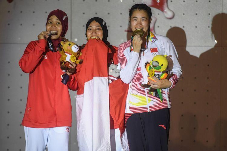 Atlet panjat tebing Indonesia peraih medali emas Aries Susanti Rahayu (tengah), Puji Lestari (kiri) dan atlet panjat tebing Cina He Cuilian (kanan) mengikuti penganugerahan medali seusai final katagori speed putri di Arena Panjat Tebing Jakabaring Sport City, Palembang, Sumatera Selatan, Kamis (23/8). ANTARA FOTO/INASGOC/Hendra Nurdiyansyah/nym/18.