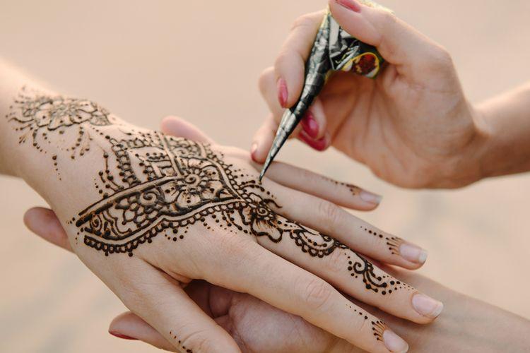 Artis menerapkan tato henna di tangan wanita. Mehndi adalah seni dekoratif tradisional India. Close-up