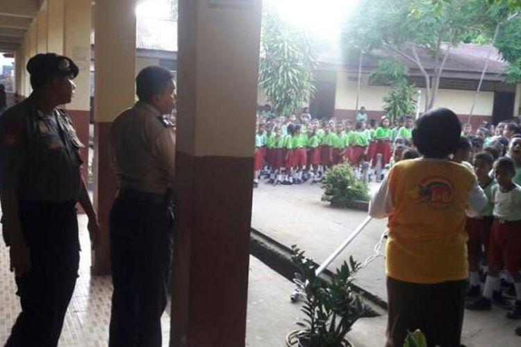 Polisi berbincang dengan seorang guru SD Inpres 21 Ambon yang mengamankan sebuah bendera Republik Maluku Selatan yang berkibar di tiang bendera sekolah tersebut, Jumat (27/1/2017) pagi.