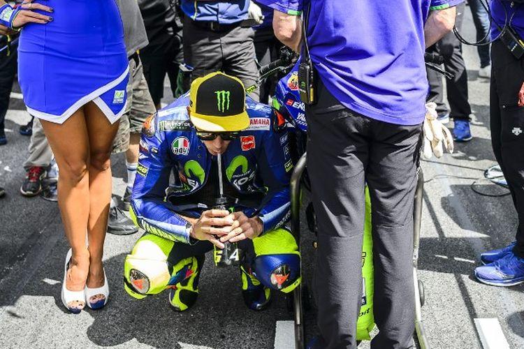 Kebiasaan yang dilakukan Valentino Rossi sebelum memulai balapan. (Photo by Jure Makovec / AFP)