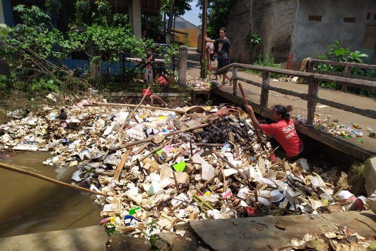Warga Rt 01 RW 04 Kelurahan Cipayung Jaya, Kecamatan Cipayung, Kota Depok, sejak pagi bergotong-royong membersihkan sampah yang tersangkut di jembatan, Jumat (17/9/2021).