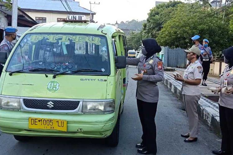 Aparat Polresta Pulau Ambon dan Pulau-Pulau Lease membagikan makanan gratis kepada sopir angkot dan penumpang angkot yang melintas di Jalan dr Latumeten Ambon, Jumat (17/4/2020)