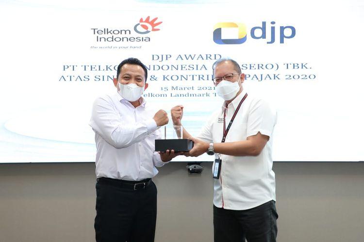 Direktur Keuangan Telkom Heri Supriadi (kanan) menyerahkan cindera mata kepada Kepala KPP Wajib Pajak Besar Empat Budi Prasetya saat acara penyerahan apresiasi kepada PT Telkom Indonesia (Persero) Tbk (Telkom) atas sinergi dan kontribusi pajak di tahun 2020 di Jakarta, Senin (15/3/2021).