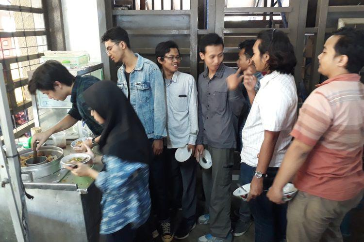 Sejumlah mahasiswa mengantre dengan berbaris untuk mengambil bakso di Bakso Pak Dhi, Kantin Arsitektur ITS, Surabaya.