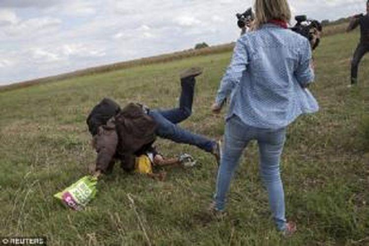 Pria pengungsi jatuh ke tanah dengan anaknya berada di bawahnya sementara perempuan juru kamera yang menendangnya menonton. Adegan ini terjadi di dekat perbatasan Hongaria dengan Serbia saat para migran dari Timur Tengah lari dari kejaran polisi Hongaria.