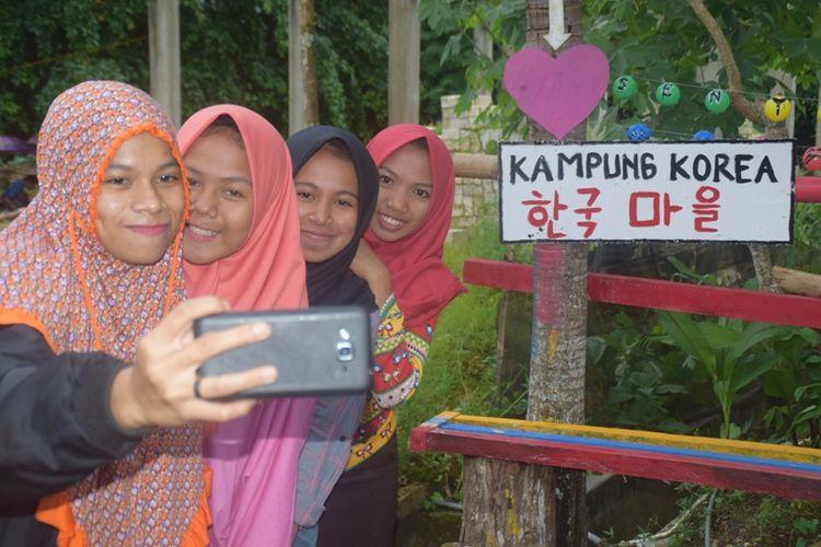 Warga lakukan foto selfie di Kampung Korea yang berada di Kampung Bugi, Kecamatan Sorawolio, Kota Baubau, Sulawesi Tenggara, Senin (28/1/2019).