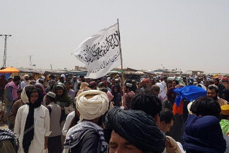 Orang-orang berkumpul di sekitar bendera Taliban saat mereka menunggu kerabat dibebaskan dari penjara di Afghanistan menyusul 'amnesti' oleh Taliban, dekat titik perbatasan Pakistan-Afghanistan di Chaman pada 17 Agustus 2021.