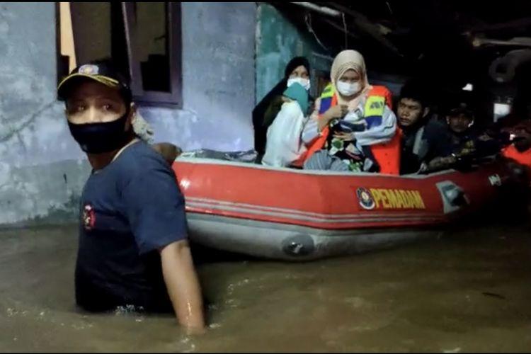 petugas pemadam kebakaran dari Suku Dinas Penanggulangan Kebakaran dan Penyelamatan (Sudin Gulkarmat) Jakarta Selatan Sektor V Cilandak mengevakuasi bayi prematur bersama orangtuanya menggunakan perahu karet di Jalan Kemang Selatan XII, Cipete Selatan, Cilandak, Jakarta, Senin (5/10/2020) dini hari.