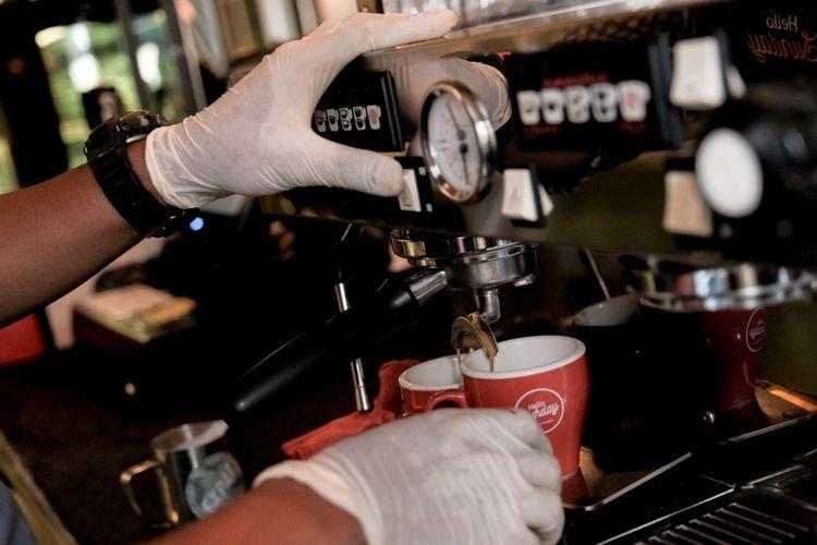 ILUSTRASI - Karyawan sebuah kedai kopi menggunakan sarung tangan saat mengoperasikan mesin espresso.