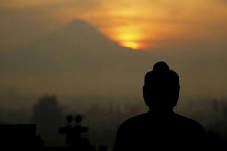 Pemandangan matahari terbit dari balik Gunung Merapi dengan latar depan patung Buddha di Candi Borobudur, Magelang, Jawa Tengah, Rabu (20/4/2011). Wisatawan yang ingin melihat pemadangan matahari terbit harus ada di candi pukul 04.30. Wisatawan lokal dikenakan biaya Rp 220.000.