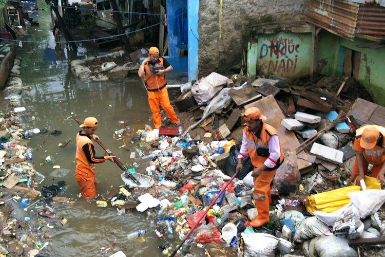 Petugas PPSU membersihkan sampah akibat banjir di RW 003 Kampung Pulo, Kelurahan Kampung Melayu, Jakarta Timur, Minggu (23/2/2020).