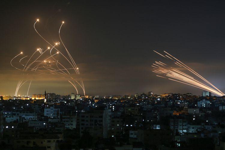 Sistem pertahanan rudal Iron Dome Israel (kiri) mencegat roket (kanan) yang ditembakkan oleh gerakan Hamas menuju Israel selatan dari Beit Lahia di Jalur Gaza utara seperti yang terlihat di langit di atas Jalur Gaza semalam pada 14 Mei 2021.