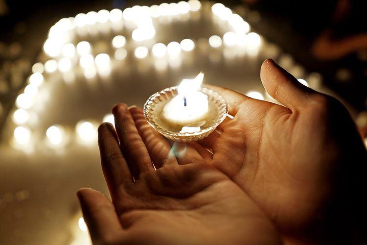 Sejumlah karyawan mematikan lampu dan menyalakan lilin pada peringatan Earth Hour di halaman Hotel Horison Nayumi, Kota Gorontalo, Gorontalo, Sabtu (30/3/2019). Aksi mematikan listrik selama 60 menit tersebut menjadi simbol yang menunjukan solidaritas untuk planet bumi serta mengurangi laju perubahan iklim.